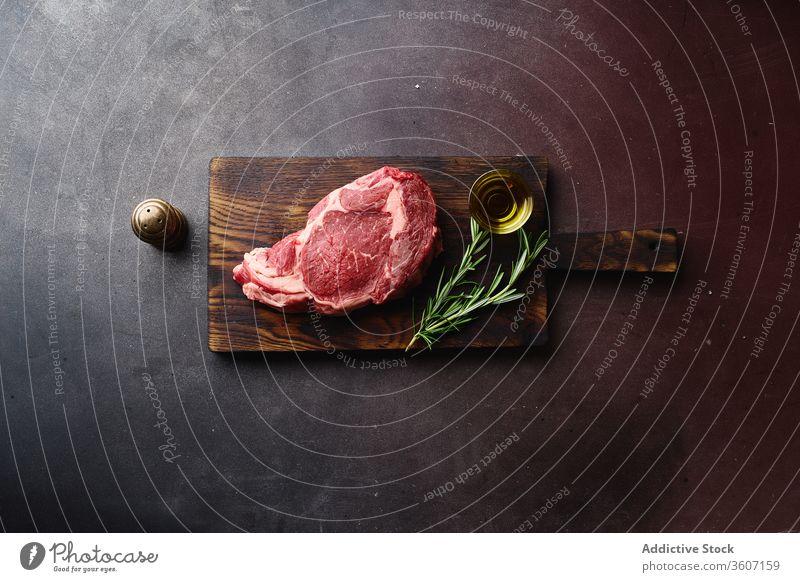 Raw beef meat on table black angus steak beefsteak flat lay barbecue food cooking raw cut ribeye marbled rib eye uncooked gourmet surface filet top view chop