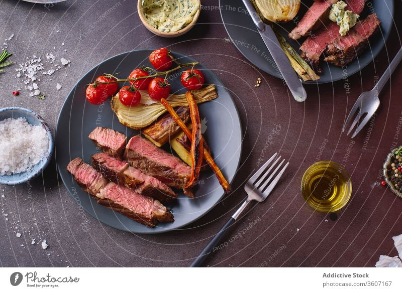 Dish of cooked beef meat on table ribeye steak grilled black angus food cuisine spice beefsteak roasted tasty sliced closeup salt cooking filet protein fresh