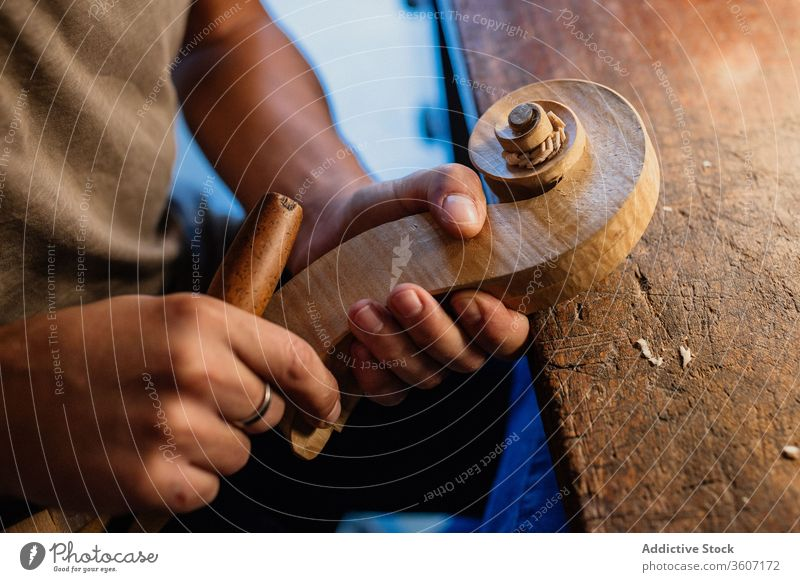 Crop workman crafting violin head using chisel in modern work studio carving craftsman tool workshop hand process handmade swirl bit wooden shape creative