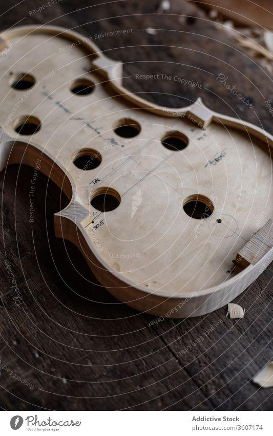Soundboard of handmade violin on shabby wooden surface in workroom soundboard process workshop hole tool craft sawdust instrument workmanship create detail