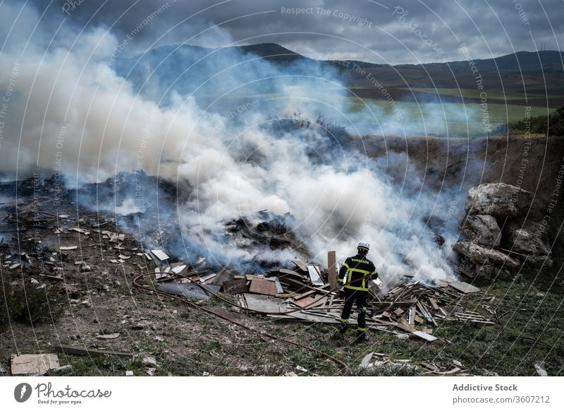 Firefighter putting out fire with water firefighter fireman brave hose extinguish smoke put out uniform male protect work equipment job stand occupation helmet