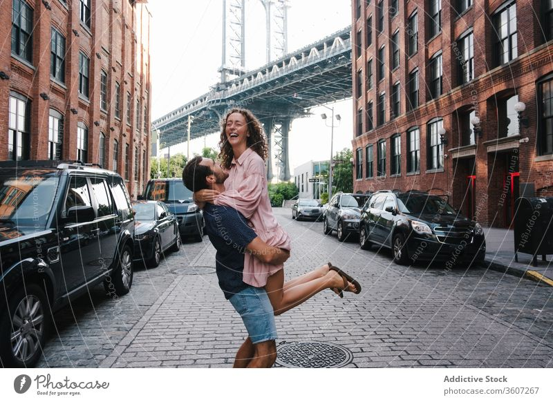 Happy couple hugging and kissing on sidewalk in city lifting girlfriend together boyfriend street love happy new york america united states usa relationship