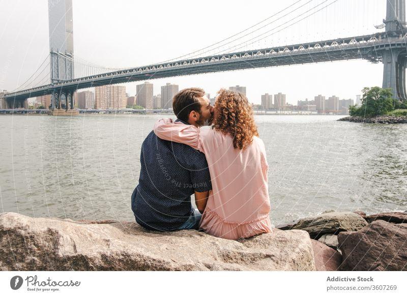 Tender couple kissing on river bank in New York relationship together romantic hug brooklyn bridge tender stroll new york america united states usa city love