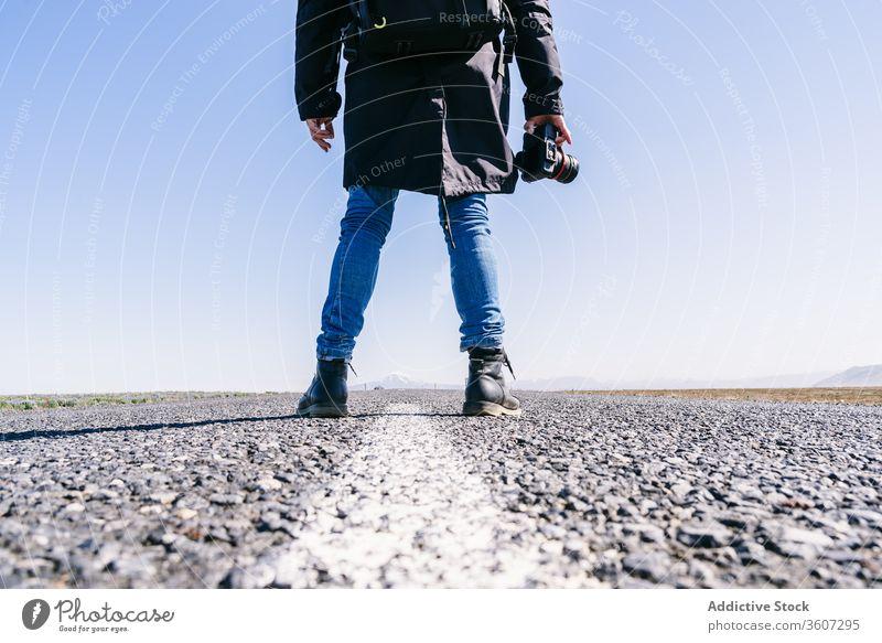 Crop male photographer on road man professional traveler landscape picturesque asphalt photo camera cold iceland photography roadway adventure outerwear season
