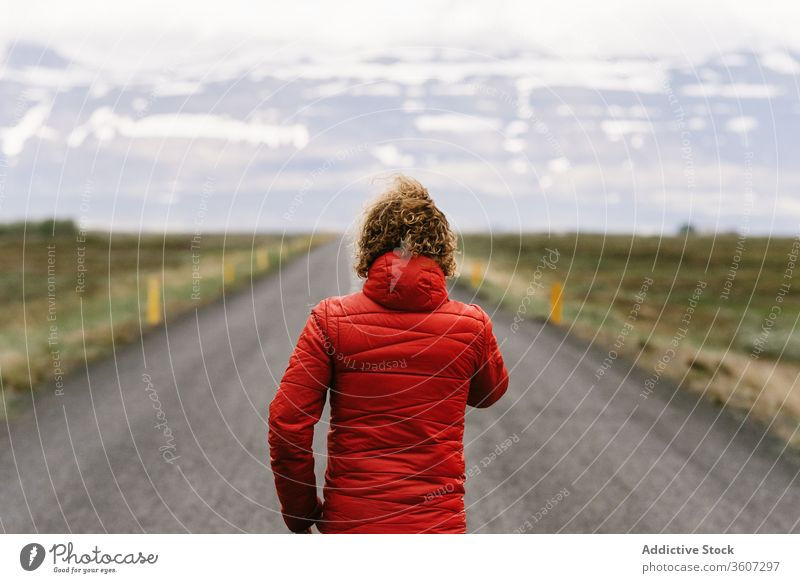 Lonely anonymous male tourist walking along road traveler mountain man roadway scenic asphalt winter iceland empty scenery nature adventure snow cold season