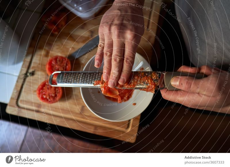 Aerial view of hands of a man grating tomato on top of a piece of wood in a kitchen aerial perspective action preparing tupperware dinner meal tiles traditional