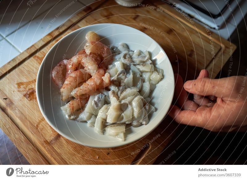 Dish with peeled prawns and cut cuttlefish on top of a wooden board kitchen ingredients paella chunks table tradition meal pieces traditional typical life