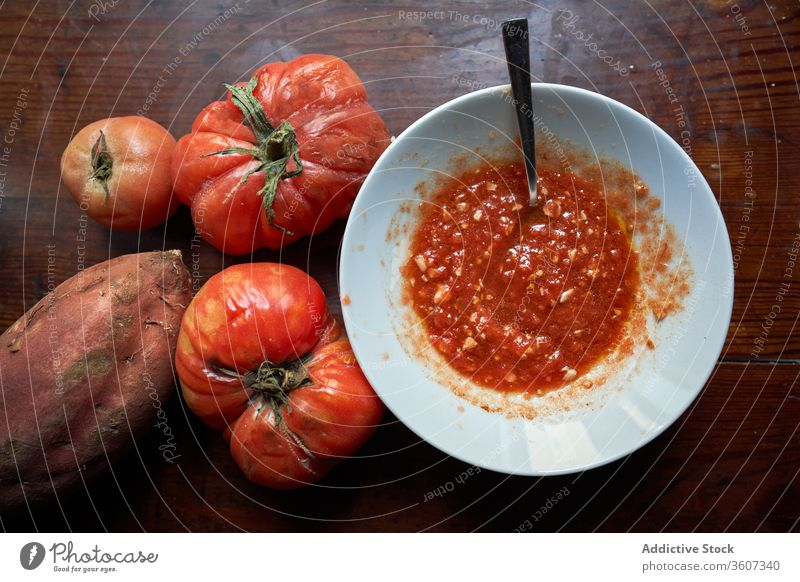 Dish with grated tomato and a teaspoon inside with two tomatoes on the side and a sweet potato organic eco farm traditional wood full table aerial perspective