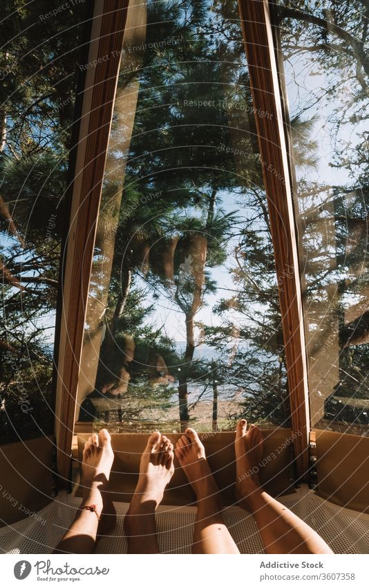 Crop couple relaxing in house in forest cam hammock together lying vacation admire girlfriend boyfriend camp relationship enjoy love cozy romantic wood window