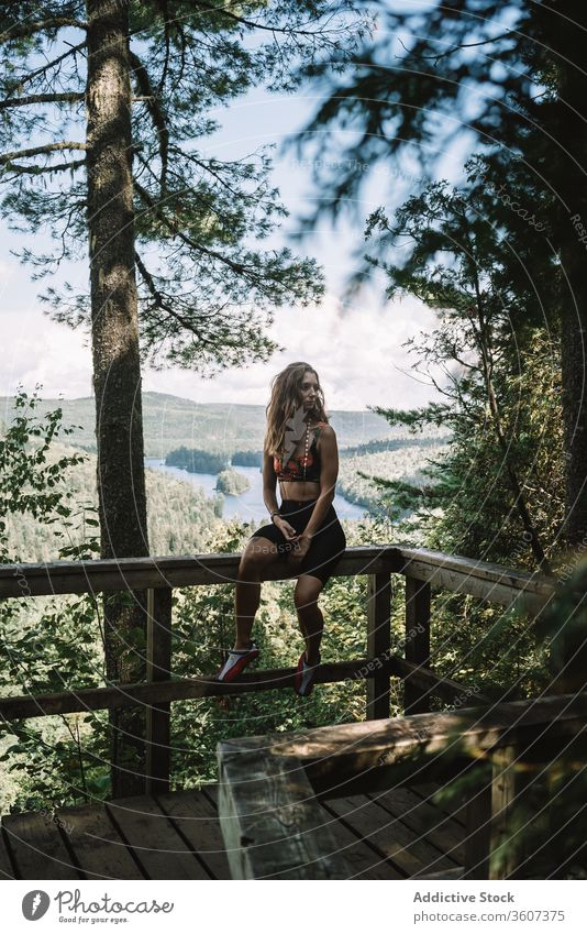 Woman resting on terrace in forest woman nature railing sit summer national park la mauricie quebec canada female travel tourist wooden relax tree vacation