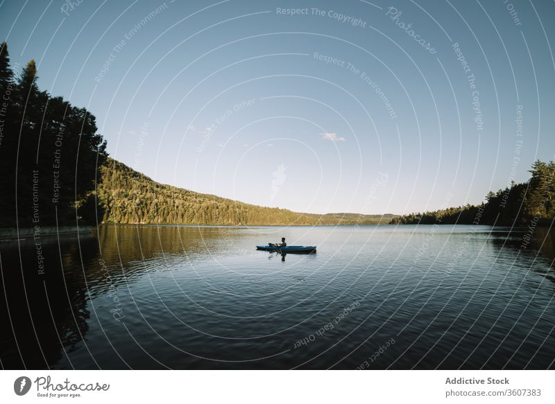 Unrecognizable man rowing boat on river kayak travel oar silhouette cloudless national park la mauricie quebec canada trip calm lake serene tranquil rest water