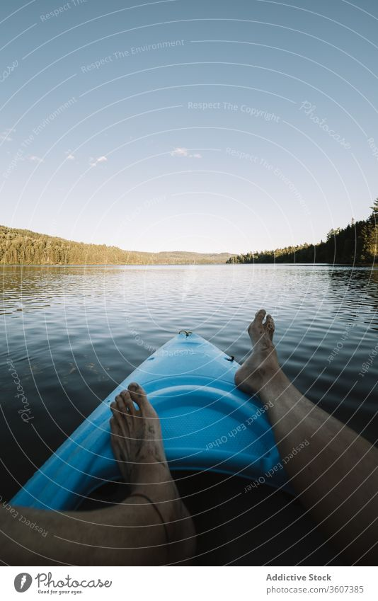 Unrecognizable traveler resting on kayak river explore water float barefoot national park la mauricie quebec canada sky cloudless boat trip nature vacation