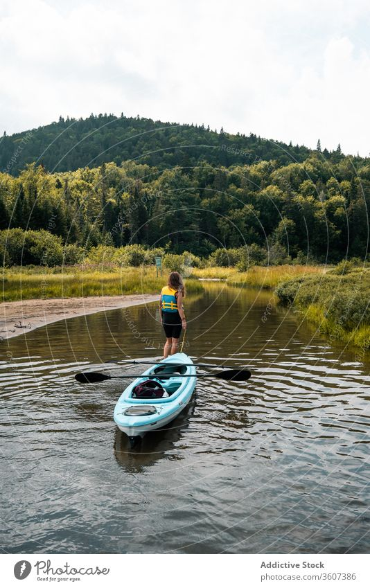 Anonymous woman with boat standing in river hill nature admire travel national park la mauricie quebec canada clean coast kayak water green trip journey