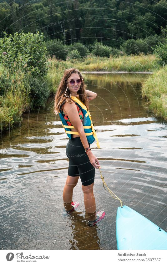 Woman with boat standing in river woman hill nature admire travel national park la mauricie quebec canada clean coast kayak water green trip journey vacation