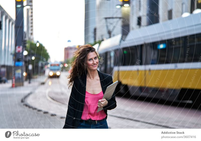 Businesswoman with laptop on city street entrepreneur businesswoman confident cityscape formal well dressed professional female cheerful content smile determine