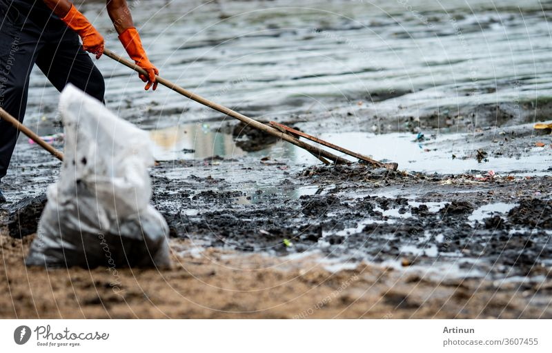 Volunteers use the rake to sweep the trash out of the sea. ฺBeach cleaner collecting garbage on the sea beach in to transparent plastic bag. Volunteers cleaning the beach. Tidying up rubbish on beach.