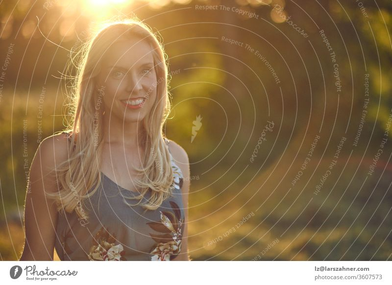 Smiling attractive blond woman backlit at sunset by the warm glow of the sun through leafy green trees in a blurred rural background with copy space sunrise