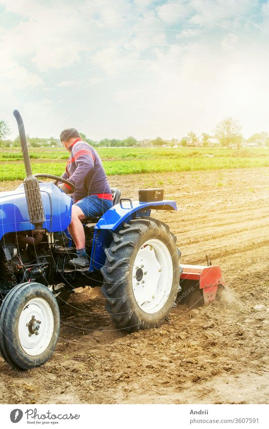 A farmer on a tractor tilling a field. The soil is ground, crumbled and mixed. Agriculture, cultivation of organic vegetables. Loosening the surface, cultivating the soil for further planting.