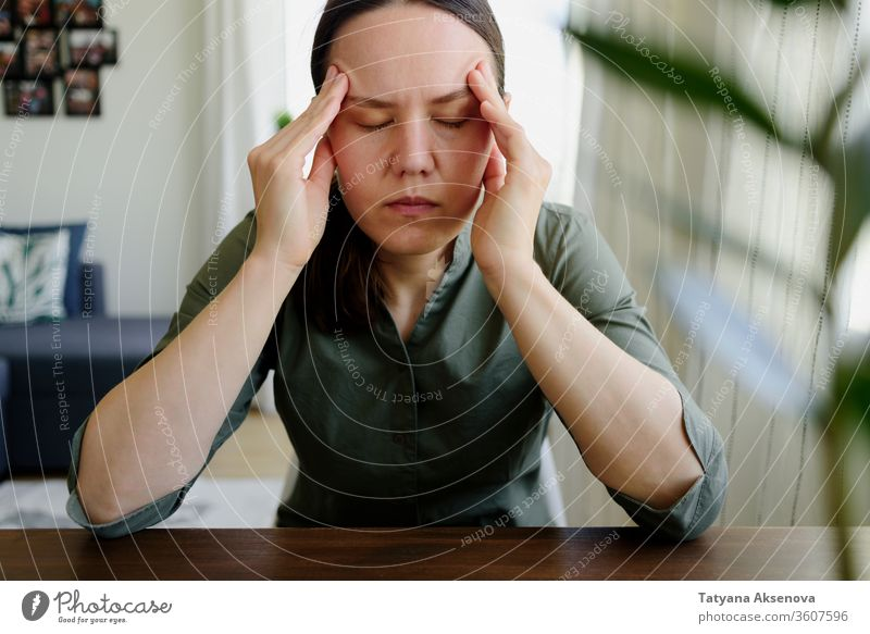 Woman thinking. Holding hands on her head. Tired, stress woman home tired praying female sad problem solving working person indoors people caucasian adult