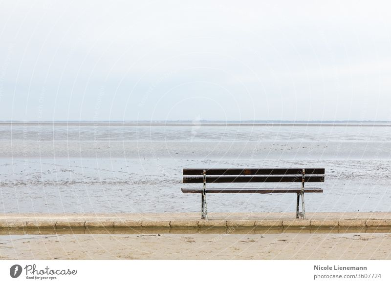 seat at north sea in germany with water, waves and sky bench beach blue ocean travel landscape nature coast summer shore cloud sand scenic outdoors grass island