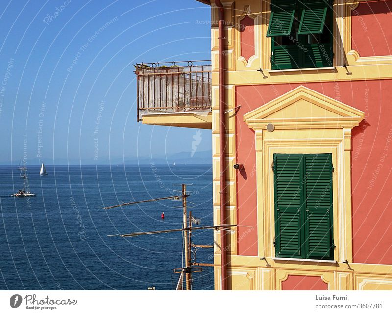 Genoa, - View of blue Tigullio gulf from the rocky cape closing Boccadasse bay and the profile of a characteristic Ligurian painted house harbor sea urban