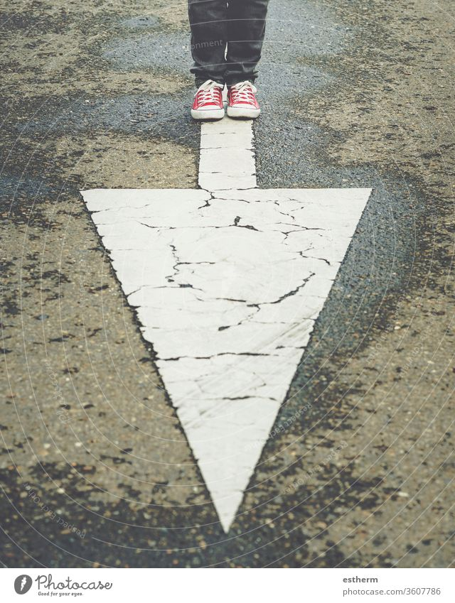 sneakers near the arrow marking of the road trendy foot people route traveler direction adventure explore footwear sign single course casual style modern