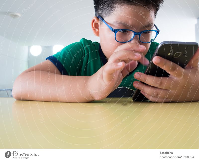 Serious boy playing on smartphone children serious game sweat asian kid hand technology telephone perspiration young earnestly internet mobile person little