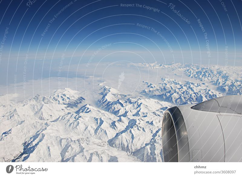 Over the mountains... Flying Airplane Mountain Snow Sky Clouds Alps Jet Engines Far-off places travel Horizon Aviation Blue Vacation & Travel Wing