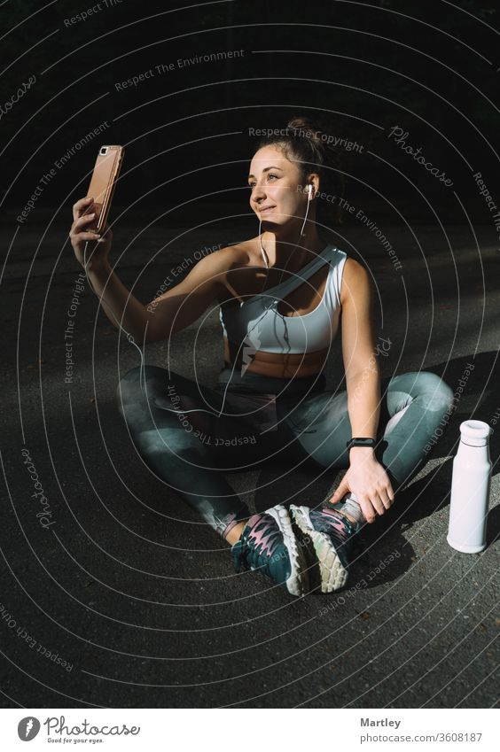Young female runner posing in sportswear taking selfie with her mobile phone. Girl enjoying an afternoon of exercise in summer and taking photos for her social networks.