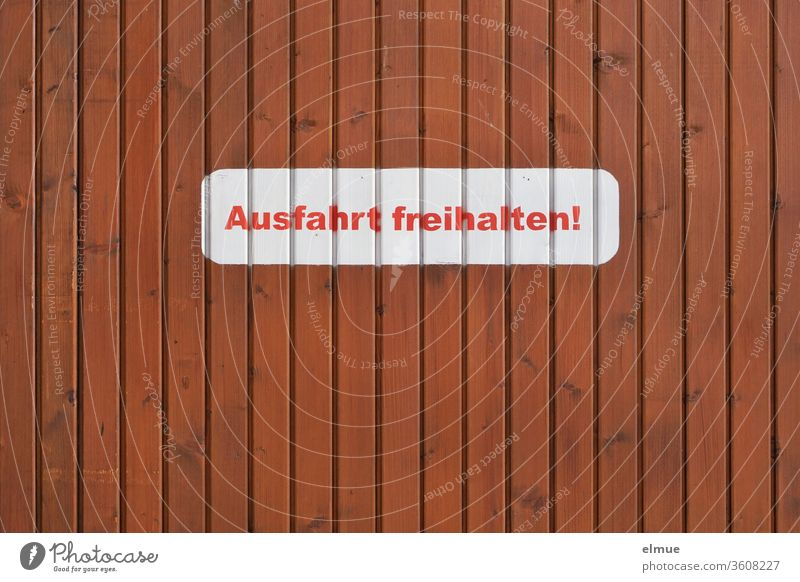 "white sticker with red print ""Keep exit free!"" on a brown wooden wall Keep the exit clear! stickers Clearway writing letter Wooden wall Private"