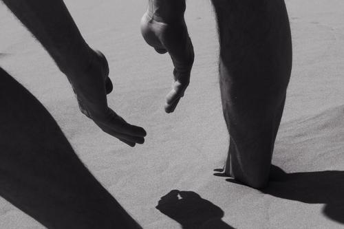 Touch of summer. Man on the beach close-up, detail of the body, gesture of hands and legs, deep shadow. Summer mood, man play with the sand. Hot weather.