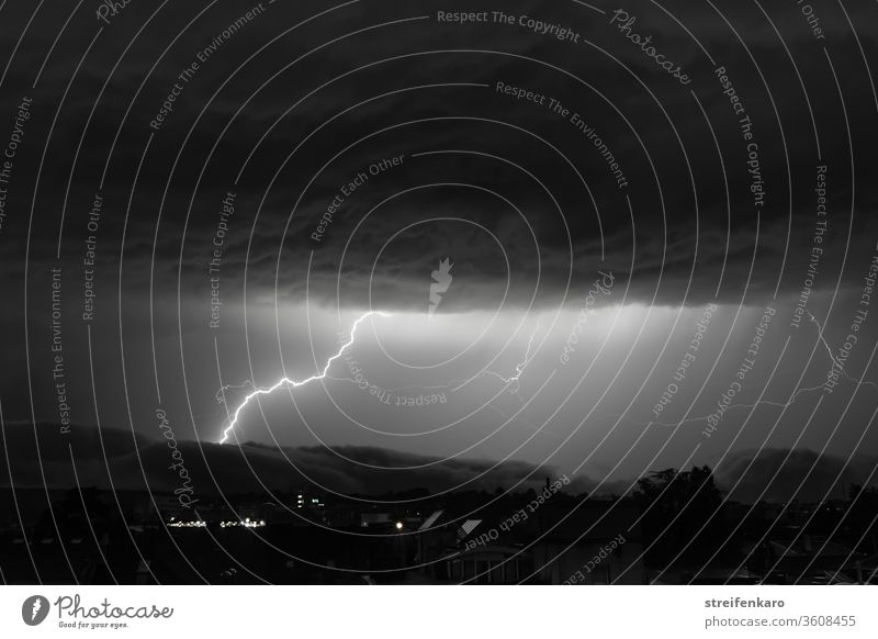 Enormous lightning can be seen in the black and white sky between the mighty cloud layers Night Thunder and lightning Lightning Storm Exterior shot Sky