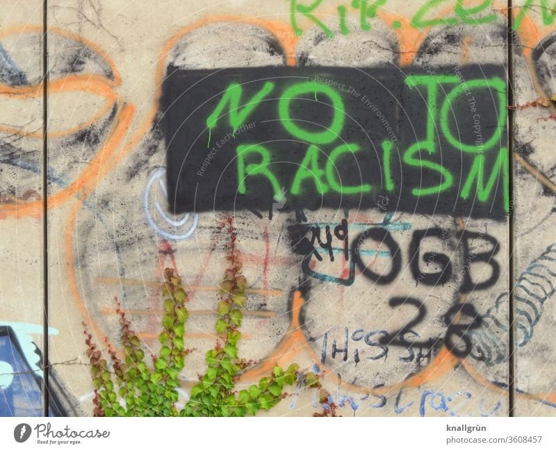 "Green graffiti ""NO TO RACISM"" on a black rectangle on a colourful wall Racism Graffiti Politics and state Society Protest protest Characters Colour photo"