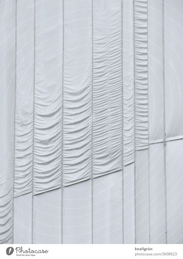 White, partly gathered long lengths of fabric cover a building that is being restored. concealment Cloth Protection Structures and shapes Pattern Gathered Folds