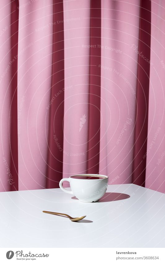 Cup of tea or coffee on white table in front of pink drapery, selective focus aroma beverage black caffeine cup curtain drink espresso hot indoors minimalism