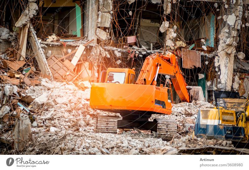 Destroyed building industrial. Building demolition by explosion. Abandoned concrete building with rubble and scrap. Earthquake ruin. Damaged or collapsed building from hurricane disaster. Backhoe.
