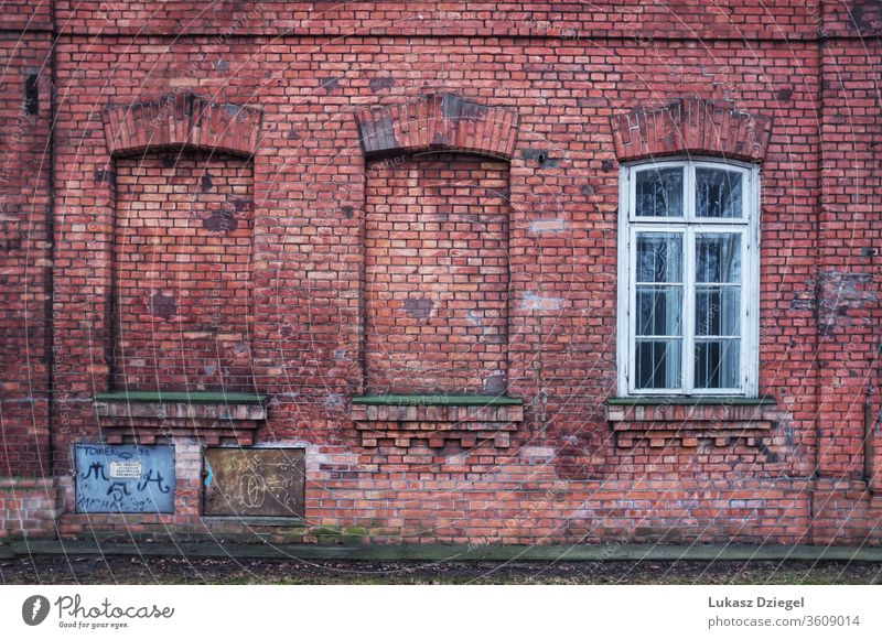 The red brick wall with three window openings, two of which have been bricked up material wall with window dilapidated vintage rust rustic retro outdoor loft