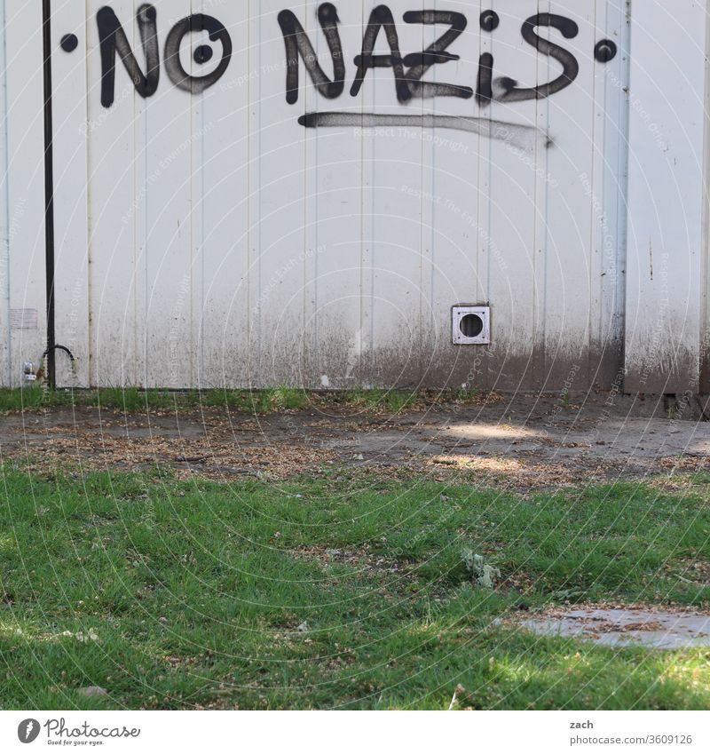 """Message """"no Nazis"""" on a white wall Graffiti Facade Wall (building) Characters built Letters (alphabet) Wall (barrier) lettering Gray Politics and state"""