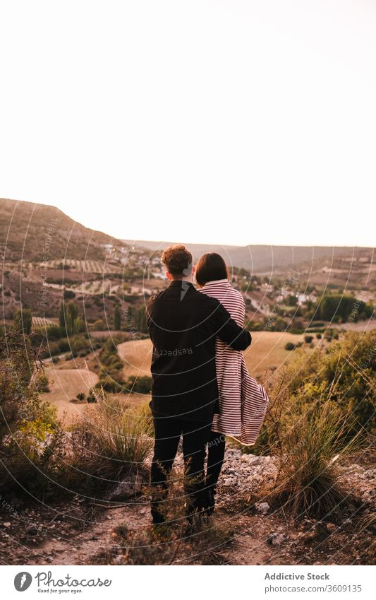 Gentle couple embracing on hill during vacation hug valley admire mountain together spectacular scenery girlfriend boyfriend plaid relationship nature love