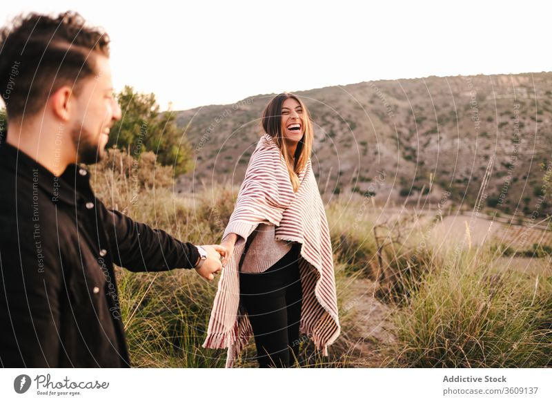 Delighted multi ethnic couple on hill laugh joke together having fun mountain holding hands cheerful relationship multiethnic multiracial diverse love