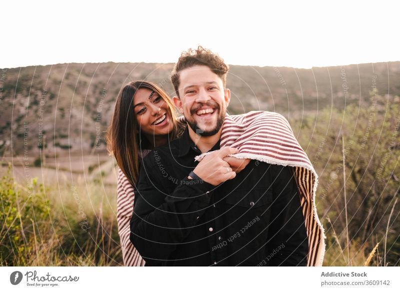 Delighted multi ethnic couple on hill laugh joke together having fun mountain hugging cheerful relationship multiethnic multiracial diverse love girlfriend
