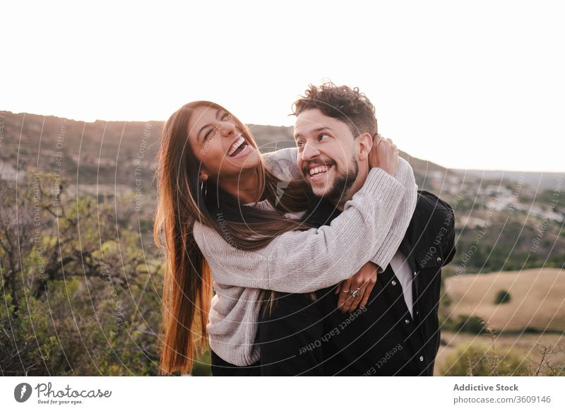 Delighted multi ethnic couple on hill laugh joke together hugging having fun mountain holding hands cheerful relationship multiethnic multiracial diverse love