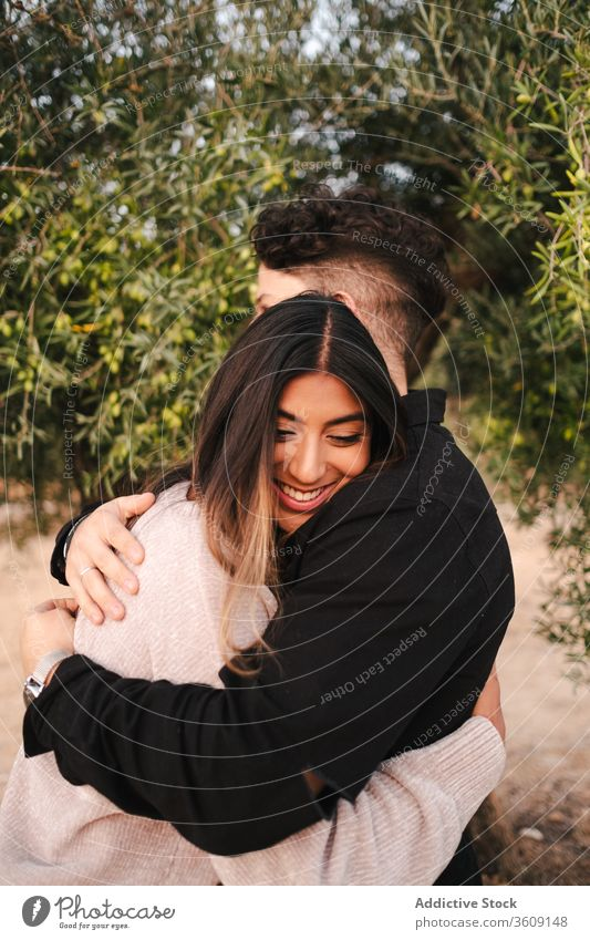 Happy multiethnic couple hugging in park garden relationship embrace love happy tender green affection multiracial diverse together nature summer bonding cuddle