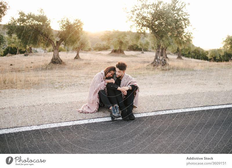 Loving couple hugging on roadside sit sunset landscape spectacular love together relationship natural romantic embrace nature happy affection romance summer
