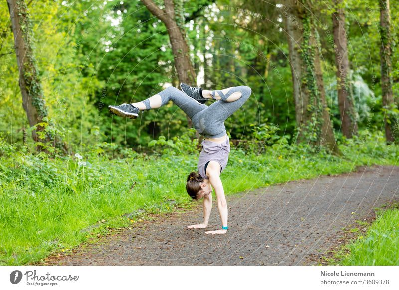 young woman doing a handstand as a fitness workout sport outdoor nature outside active movement outdoors running healthy lifestyle exercise jogging people