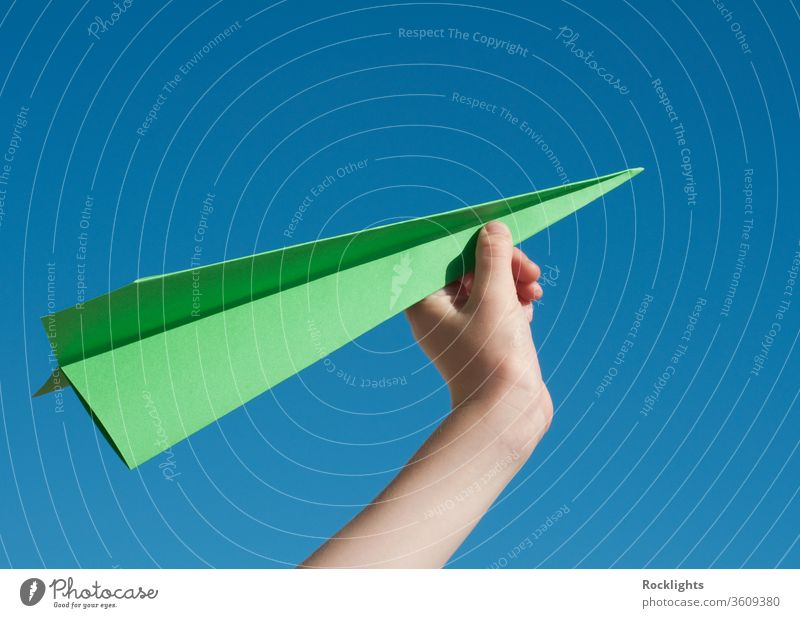 Green travel concept with a green paper airplane against blue sky Paper Airplane Aspirations aeroplane boys child flying Inspiration Sky Freedom human Hand