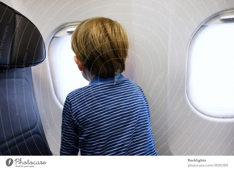 Little boy looking out of aeroplane window airplane child kid family travel little passenger holiday aircraft vacation flight tourism small people young inside