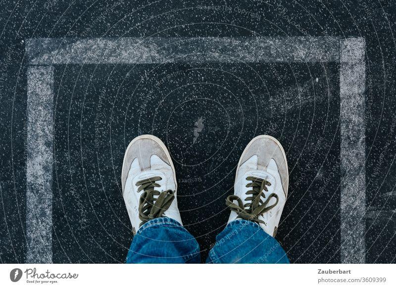 White sneakers on asphalt in rectangular boundary of white lines Line Rectangle Asphalt Border Boundary stop holds shoelaces jeans Exit route mark