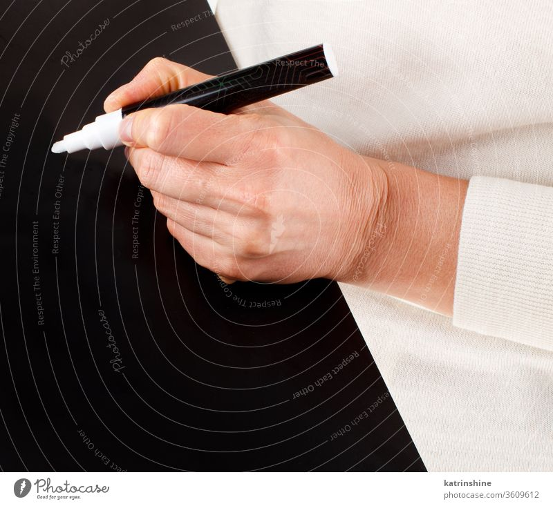 Woman writing on a black chalkboard keeping small close up hands body blackboard school educational faceless trendy