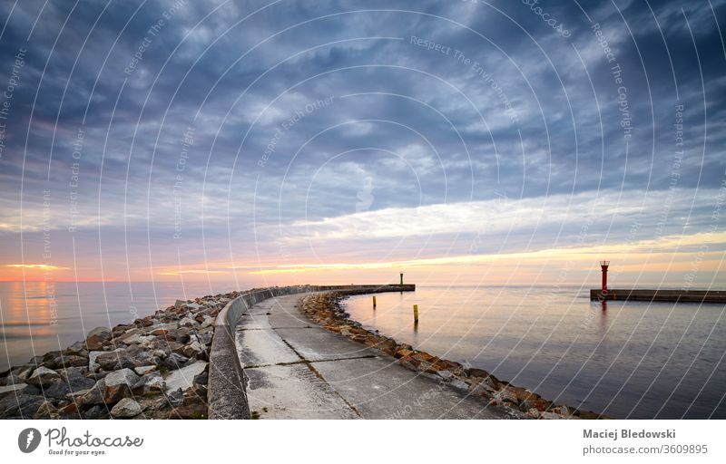 Rocky pier at the entrance to the harbor at sunset. ocean nature sea dusk navigation protection sunrise horizon dramatic storm weather seascape nautical rock